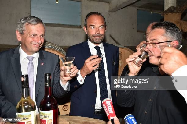French La Republique En Marche party MP JeanRene Cazeneuve French Prime Minister Edouard Philippe and wine and armagnacs producer Michel Baylac hold...