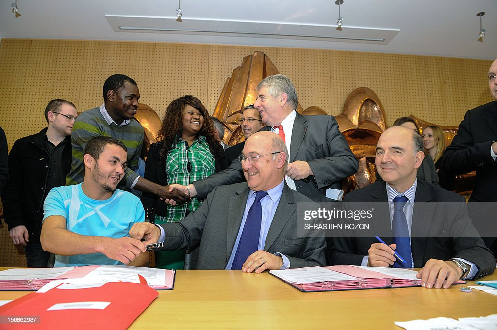French Labour, Employment and Social Dialogue Michel Sapin (C) and French Economy, Finance and Foreign Trade Minister Pierre Moscovici (R) sign with a young man a contract for future on November 23, 2012 in Besançon.