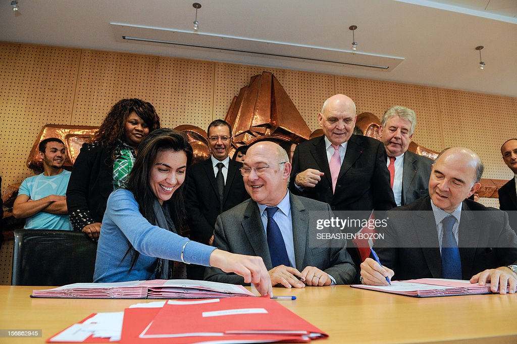 French Labour, Employment and Social Dialogue Michel Sapin (C) and French Economy, Finance and Foreign Trade Minister Pierre Moscovici (R) sign with a young woman a contract for future on November 23, 2012 in Besançon. AFP PHOTO / SEBASTIEN BOZON