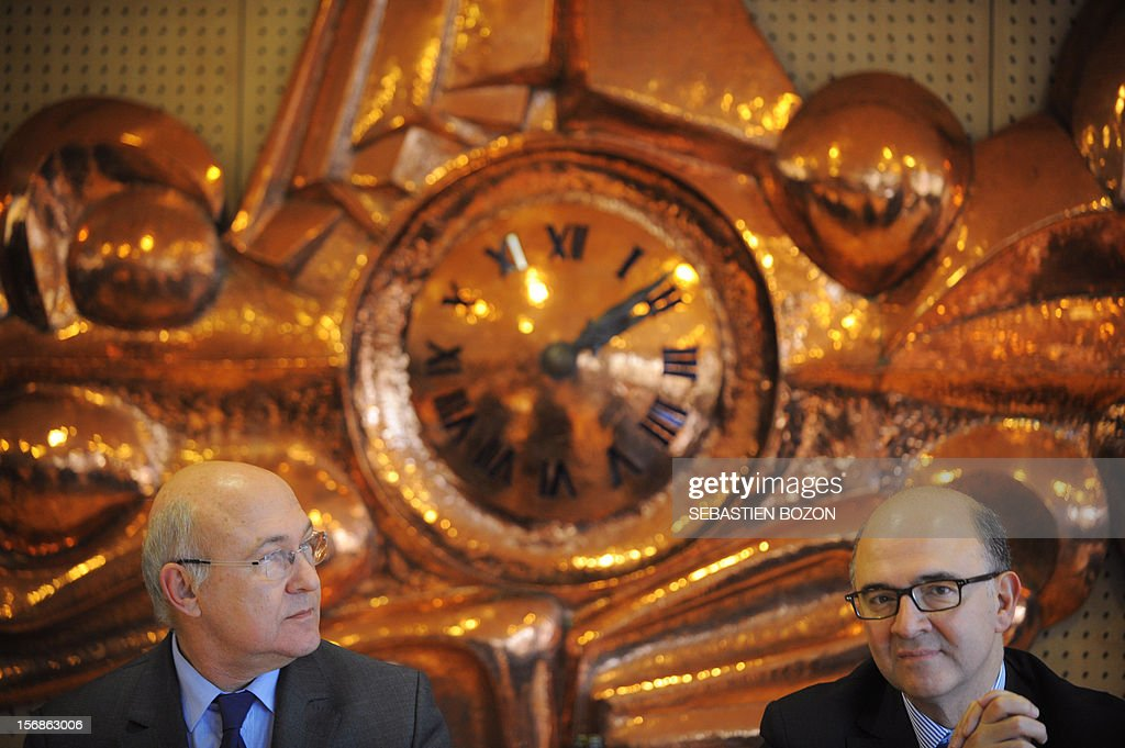 French Labour, Employment and Social Dialogue Michel Sapin (L) and French Economy, Finance and Foreign Trade Minister Pierre Moscovici (R) listen to a speech at the Conseil general du Doubs, on November 23, 2012 in Besançon.
