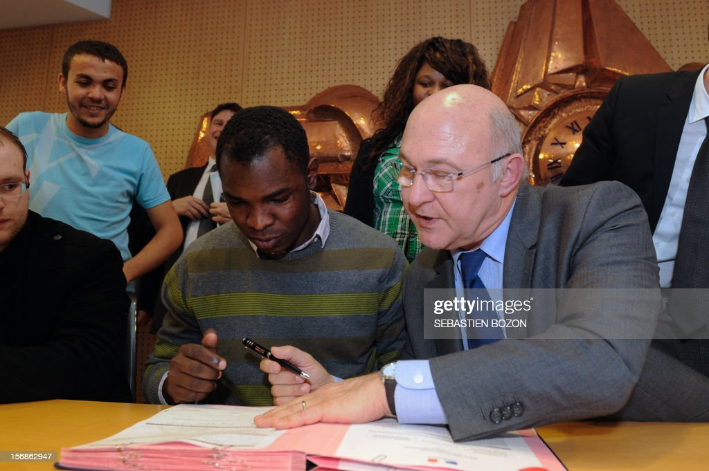 French Labour, Employment and Social Dialogue Michel Sapin (R) signs with a young man a contract for future on November 23, 2012 in Besançon.