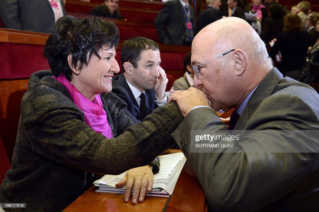 French Labour, Employment and Social Dialogue Minister, Michel Sapin kisses the hand of Junior Minister for Family, Dominique Bertinotti (L) during a National conference against Poverty and for the social Inclusion (Conference nationale contre la pauvrete et pour l'Inclusion sociale), on December 10, 2012 in Paris.