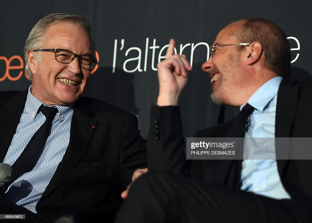French Labour minister Francois Rebsamen (R) and French telecom operator Orange CEO Stephane Richard (L) smile during a visit at the French telecom operator Orange company in Villeurbanne near Lyon, on February 6, 2014.