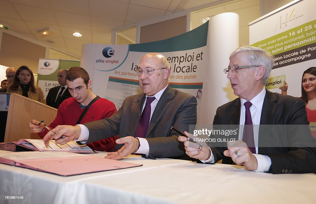 French Labour Minister Michel Sapin (C), flanked by the director of Paris Habitat Jean-Yves Mano (R), sits with a job-seeker before signing a new job convention at a Pole Emploi state employment agency on February 14, 2013 in Paris. The number of unemployed has risen steadily in France for the past 20 months, and could soon reach the record high set in January 1997 of 3.2 million.