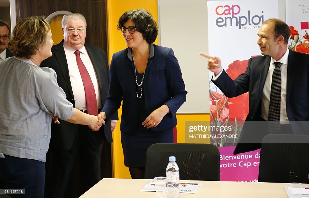 French Labour minister Myriam El-Khomri (C), flanked by Mayor of the 19th district of Paris Francois Dagnaud (R) and Member of Parliament Daniel Vaillant (2ndL), shakes hands with a job seeker as she visits Cap Emploi, France's national employment agency for disabled people, on May 25, 2016 in Paris. / AFP / MATTHIEU