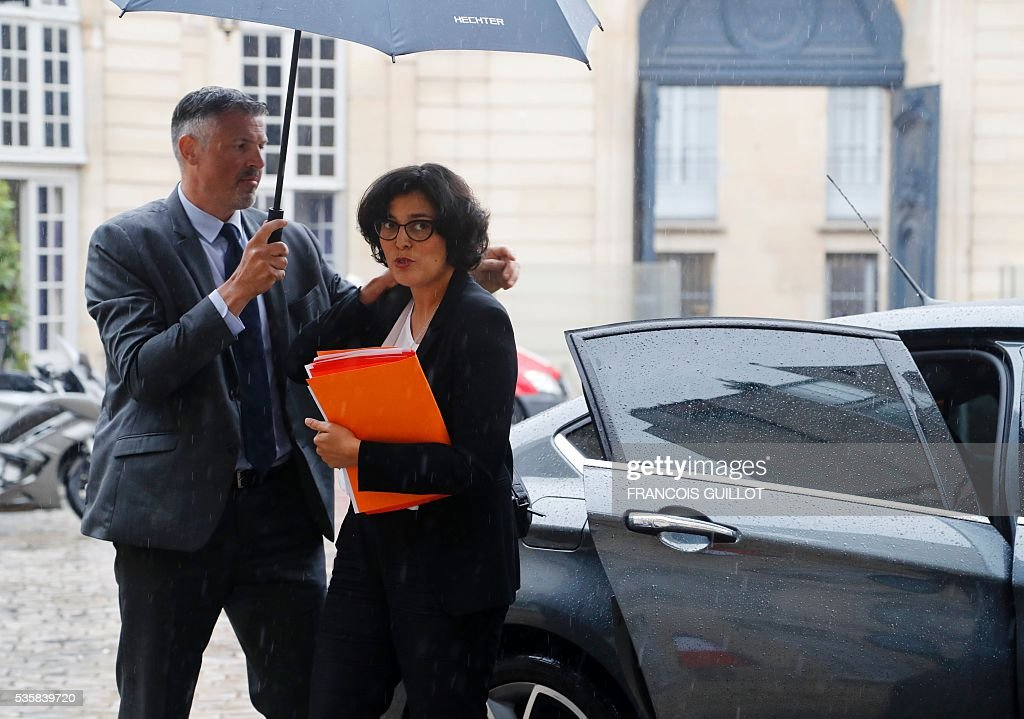 French Labour minister Myriam El-Khomri walks under an umbrella as she arrives to attend the national commission on the fight against undeclared work on May 30, 2016 at the hotel Matignon in Paris. / AFP / FRANCOIS