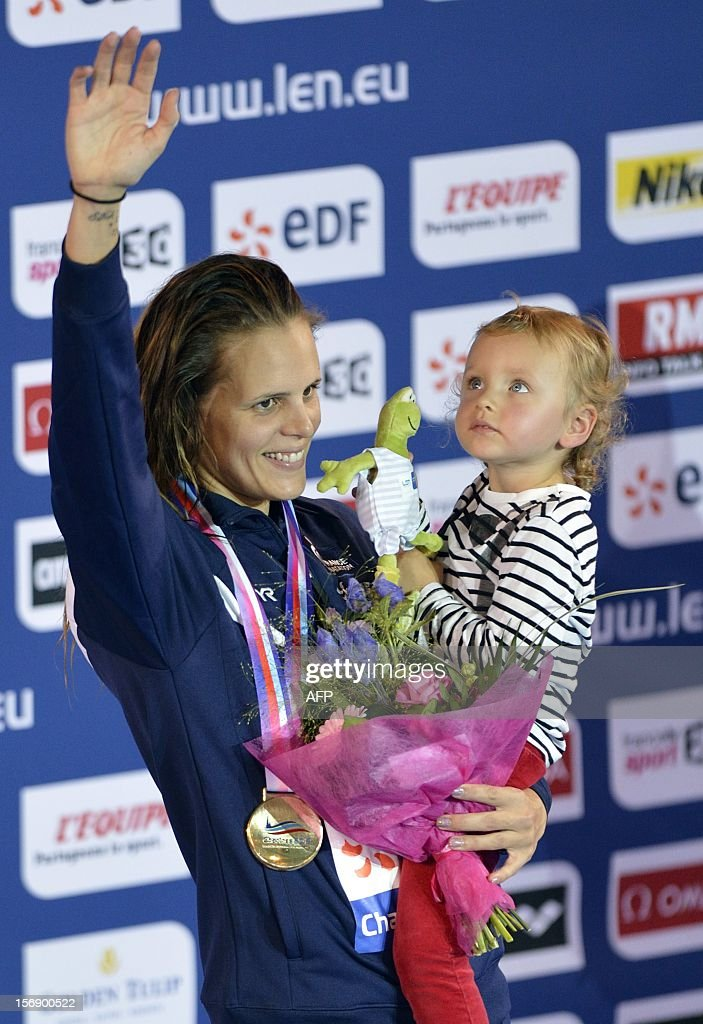 French Laure Manaudou celebrates with her daughter Manon in the arms as she receives his gold medal for the women's 50m backstroke final at the European Swimming Championships on November 24, 2012, in Chartres.
