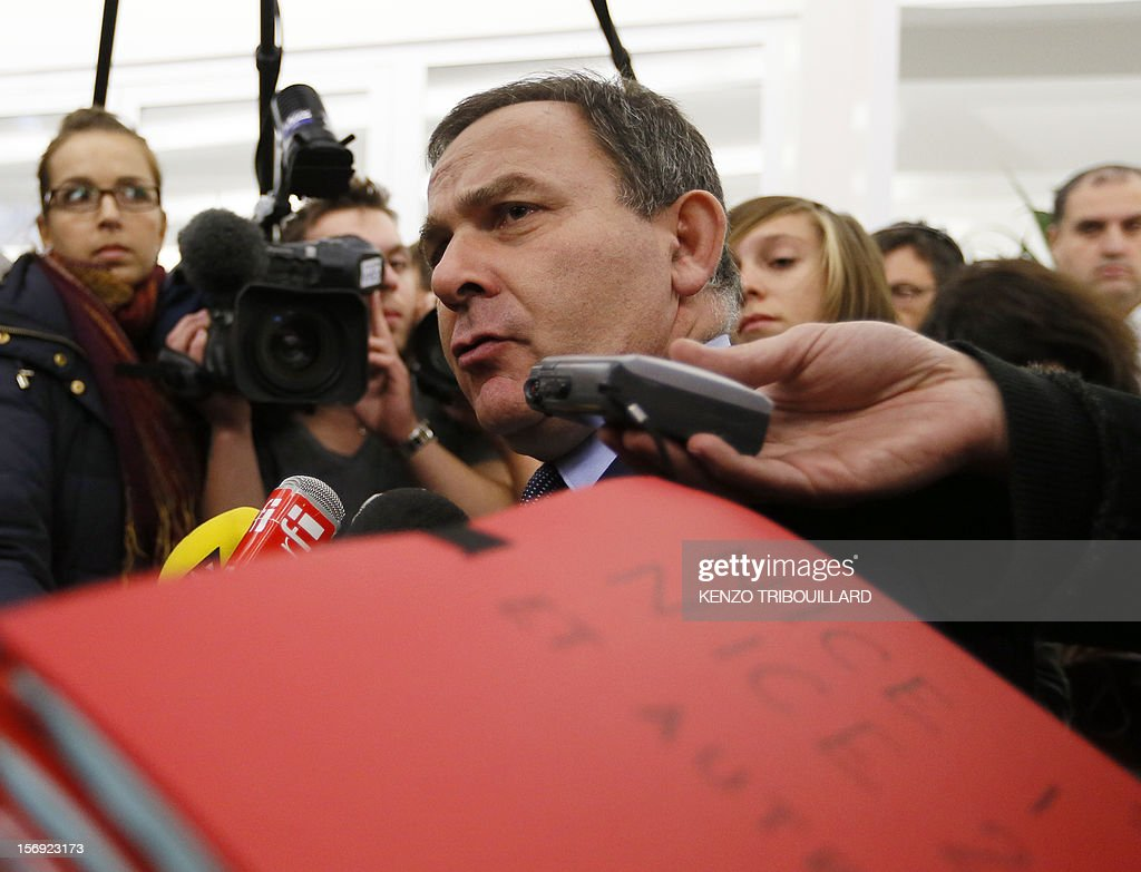 French lawyer and pro-Cope supporter, Francis Szpiner (C) answers the media in front of electoral files of the French southern town of Nice at the right-wing opposition UMP party's headquarters in Paris on November 25, 2012, after a meeting of the UMP's elections control committee (COCOE). Szpiner declared a 'desertion' the fact that French former Prime minister Francois Fillon's campaign director, Eric Ciotti slammed the door from the UMP's appeal elections control board, after considering it illegitimate and biased. Party heavyweight Juppe, a former premier and foreign minister, will hold a mediation meeting later in the day with the right-winger, who was declared the winner of November 22 knife-edge vote to pick a party leader, Jean-Francois Cope, and his centrist rival Francois Fillon. The talks are to establish who actually won the leadership and whether mutual allegations of ballot rigging have any foundation. AFP PHOTO KENZO TRIBOUILLARD