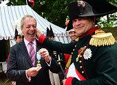French lawyer Franck Samson dressed as Napoleon Bonaparte pulls the ear of UK Independence Party leader Nigel Farage at Napoleon Bonaparte...