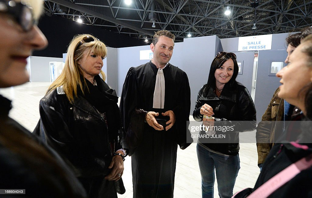 French lawyer Laurent Gaudon (C), representing women who received defective PIP breast implants, speaks to a plaintiff outside the courtroon on May 17, 2013 at the Parc Chanot in Marseille, southern France, on the last day of the trial of five managers from Poly Implant Prothese (PIP) for allegedly selling faulty breast implants that sparked global health fears. PIP company was shut down on March 2010 and its product banned after it was revealed to have been using non-authorised silicone gel that caused abnormally high rupture rates of its implants. Prosecutors are pushing for a four-year sentence for the faulty breast implant firm founder.