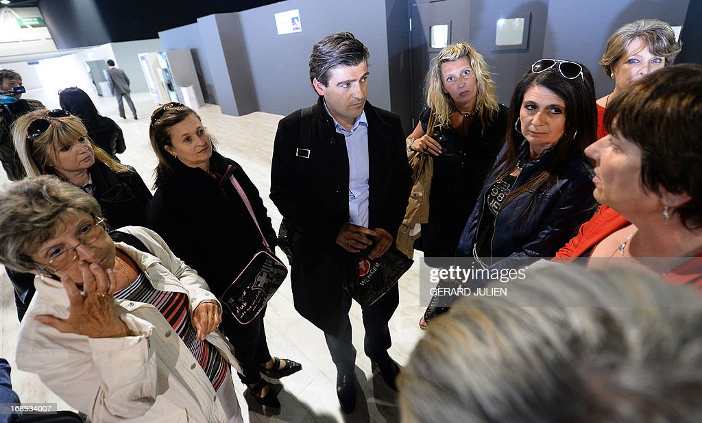 French lawyer Philippe Courtois (C) representing women who received defective PIP breast implants speaks to plaintiffs outside the courtroom on May 17, 2013 at the Parc Chanot in Marseille, southern France, on the last day of the trial of five managers from Poly Implant Prothese (PIP) for allegedly selling faulty breast implants that sparked global health fears. PIP company was shut down on March 2010 and its product banned after it was revealed to have been using non-authorised silicone gel that caused abnormally high rupture rates of its implants. Prosecutors are pushing for a four-year sentence for the faulty breast implant firm founder.