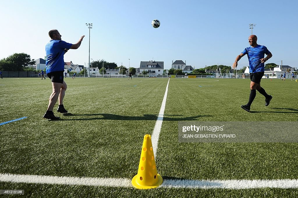French League 1 football referee Amaury Delerue (R) throws the ball to Fredy Fautrel as they take part in a training session during their internship in Quiberon, western France, on June 25, 2014, ahead of the 2014/2015 French L1 football season that will start on August 9, 2014. AFP PHOTO / JEAN-SEBASTIEN EVRARD