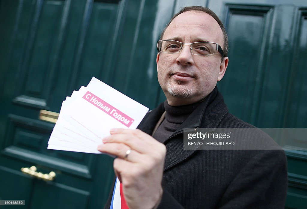 French left wing Socialist Party (PS) MP, Yann Galut, poses on January 27, 2013 in Paris, showing the new year wishes postcards, written in Russian and French, he sent in protest against French actor and other tax exiles leaving France for Russia. Galut asked for deprivation of nationality for French actor Gerard Depardieu. The card is ready 'Happy New Year'.