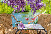 two glasses of pink wine on a table and two wicker chairs in front of the river and below the blooming purple wisteria