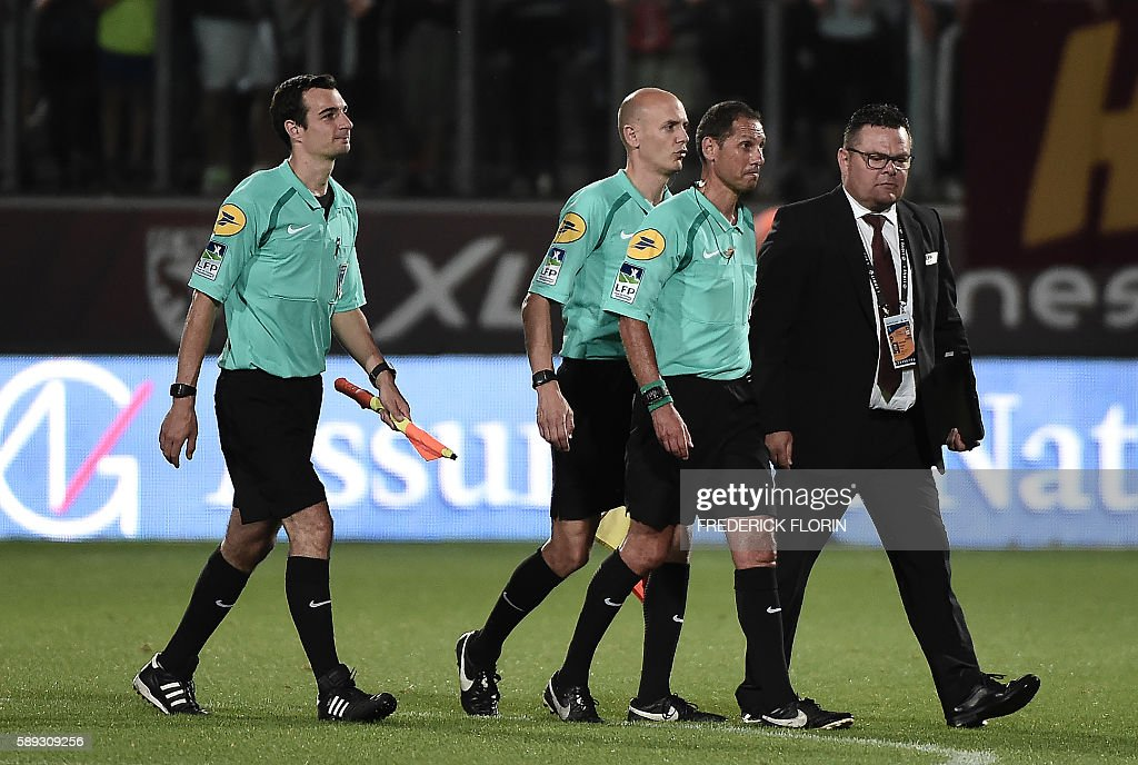 French lineman referee Julien Aube French lineman referee Sebastien Denis and French referee Mikael Lesage exit the field after the French L1...
