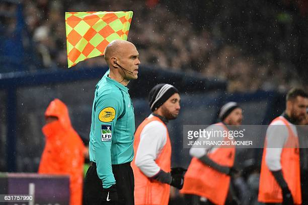 French linesman Nicolas Henninot raises his flag during the French L1 football match between Caen and Lyon on January 15 at Michel d'Ornano stadium...