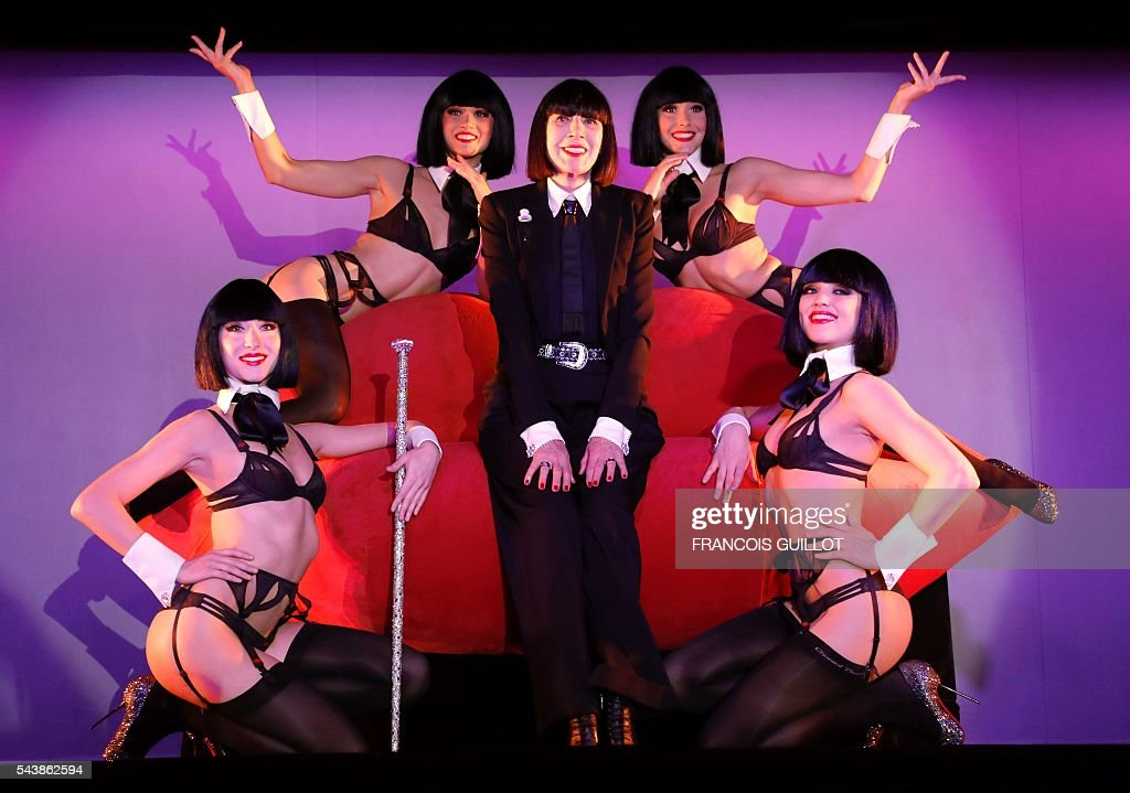 French lingerie designer Chantal Thomass (C), new guest artistic director of the Crazy Horse Paris show, poses with dancers, after a press conference in Paris on June 30, 2016. Thomass has created the costumes and sets for a new show called 'Dessous Dessus' that will run from October 5 to December 31, 2016. / AFP / FRANCOIS