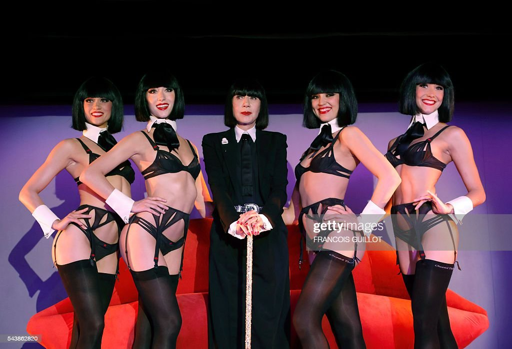 French lingerie designer Chantal Thomass, new guest artistic director of the Crazy Horse Paris show, poses with dancers after a press conference in Paris on June 30, 2016. Thomass has created the costumes and sets for a new show called 'Dessous Dessus' that will run from October 5 to December 31, 2016. / AFP / FRANCOIS