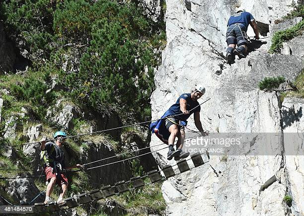 French lock Yoann Maestri jokes while passing a monkey bridge as he rock climbs with rugby French team players during a Rugby Union World Cup 2015...