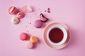 Sweet french macarons and meringues on pink background.