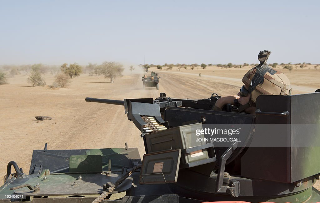 A French machine gunner of the 92nd Infantry Regiment (92eme R.I) sits in the turret of an armoured personnel carrier (VAB) as a military convoy makes its way to the village of Amakouladji north of Gao on March 10, 2013, to assess the needs of the local population there. AFP PHOTO / JOHN MACDOUGALL