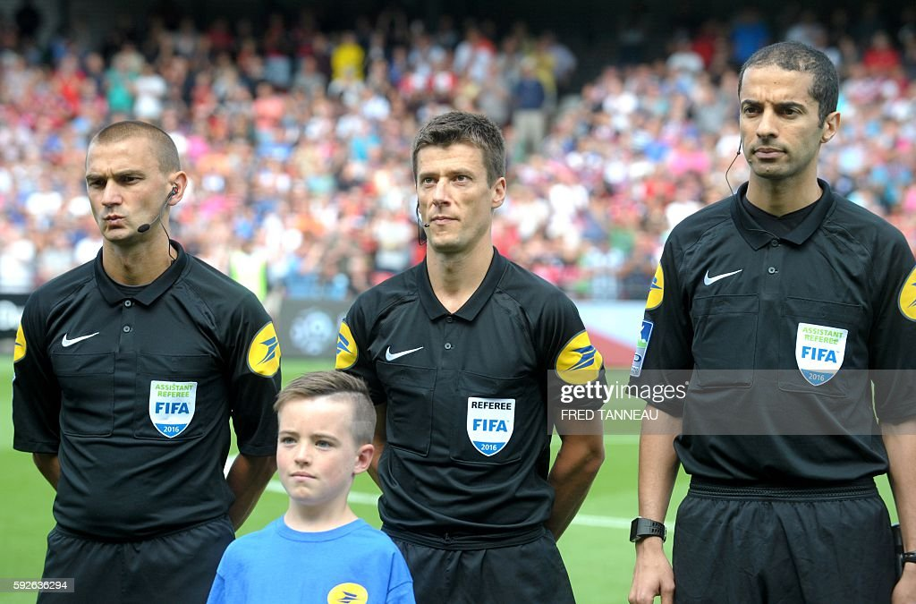 French main referee Benoit Bastien with assistant referee Frédéric Haquette and Hicham Zakrani stand prior to the French Ligue 1 football match...