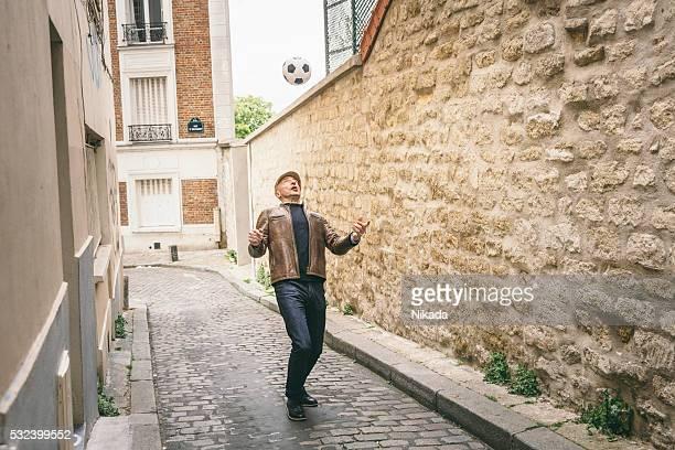 Français Homme jouant avec un ballon de football à une rue urbaine