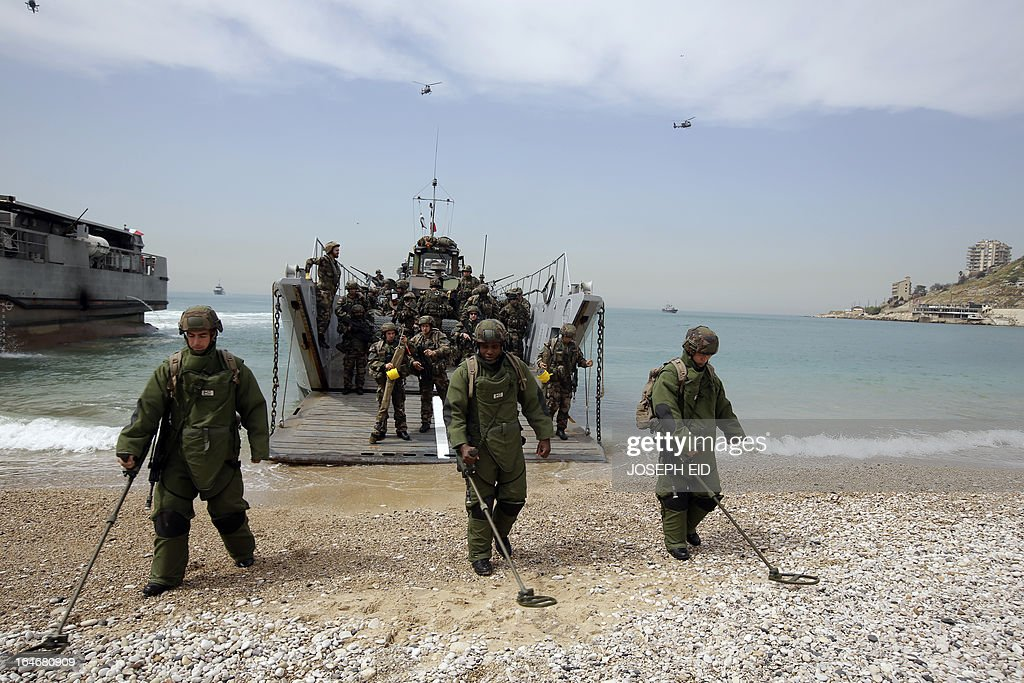 French marines use land mine detectors as they take part in sea and land war games with the Lebanese Army at the bay of Jounieh, north of Beirut, on March 26, 2013.