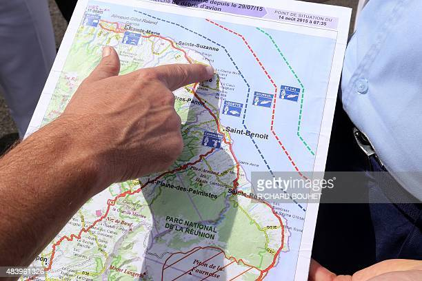 French maritime gendarmes look at a map indicating measures being undertaken in the search for wreckage from the missing MH370 plane at the marina of...