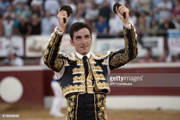 French matador Thomas Dufau holds the ears of a bull as he acknowledges spectators after fighting a Juan Pedro Domecq bull at the Plumacon Arena in...