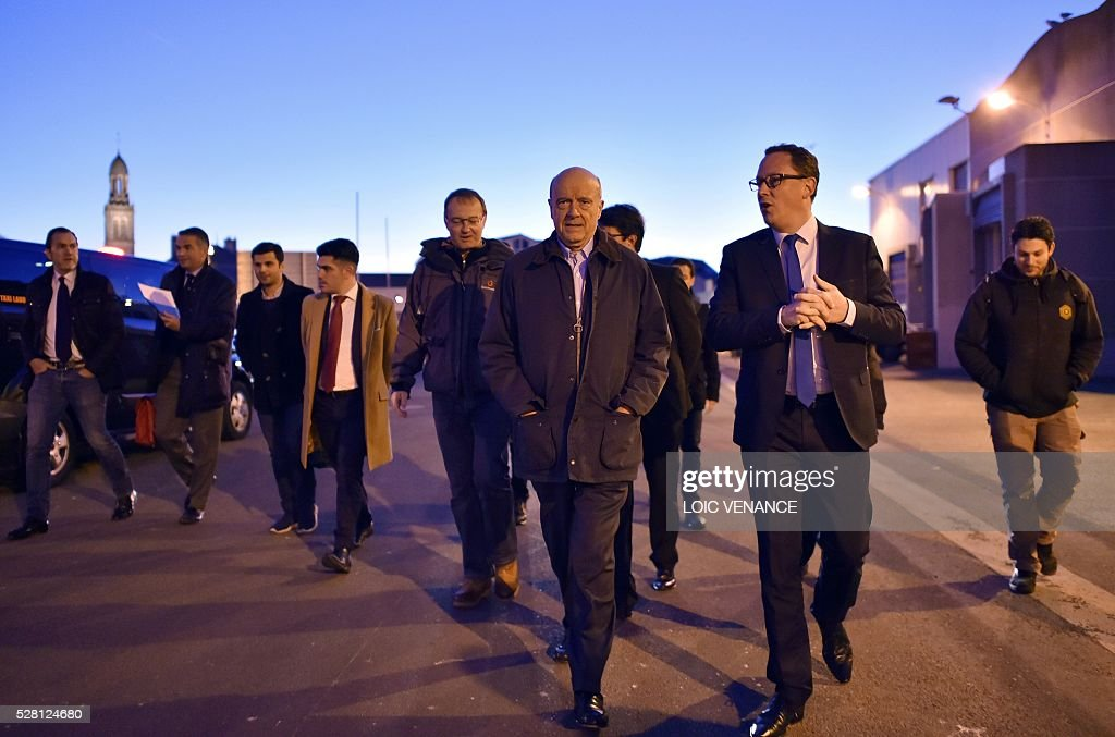 French mayor of Bordeaux and candidate for the right-wing Les Republicains (The Republicans) presidential primary Alain Juppe (C) arrives to attend a fish sale auction during a visit to Saint-Gilles-Croix-de-Vie, western France, on May 4, 2016. / AFP / LOIC