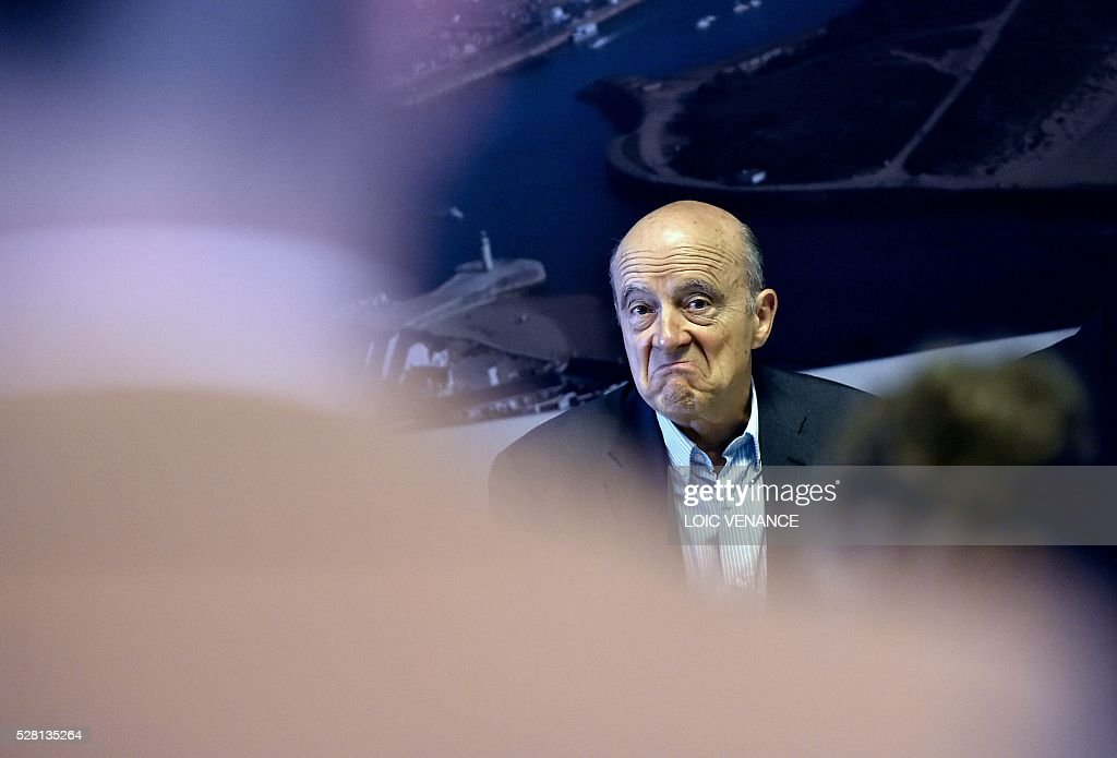 French mayor of Bordeaux and candidate for the right-wing Les Republicains (The Republicans) presidential primary Alain Juppe grimaces as he meets with fishermen during a visit to Saint-Gilles-Croix-de-Vie, western France, on May 4, 2016. / AFP / LOIC