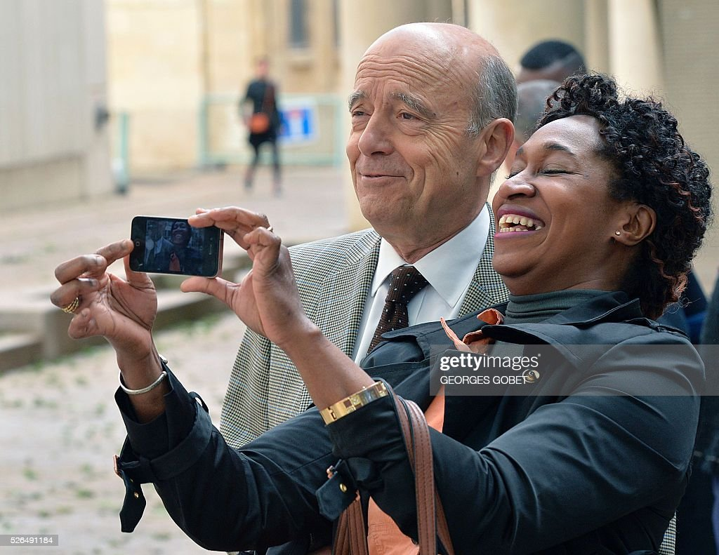 French Mayor of Bordeaux and French candidate for the right-wing Les Republicains (The Republicans) presidential primary Alain Juppe poses for a picture with a woman as he leaves the Joseph Wresinski room after the opening ceremony of the 4th edition of the Days of African diaspora on April 30, 2016 in Bordeaux. The event Days of African diaspora lasts two days during which debates about the role of diaspora and its contribution to the developement of the African continent will take place. / AFP / GEORGES