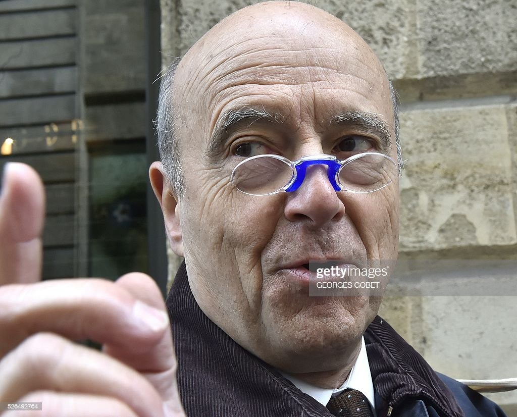 French mayor of Bordeaux and French candidate for the right-wing Les Republicains (The Republicans) presidential primary Alain Juppe tries a pair of lorgnon received by a seller during the promotional launching of a shopping street in the city centre of Bordeaux on April 30, 2016. / AFP / GEORGES