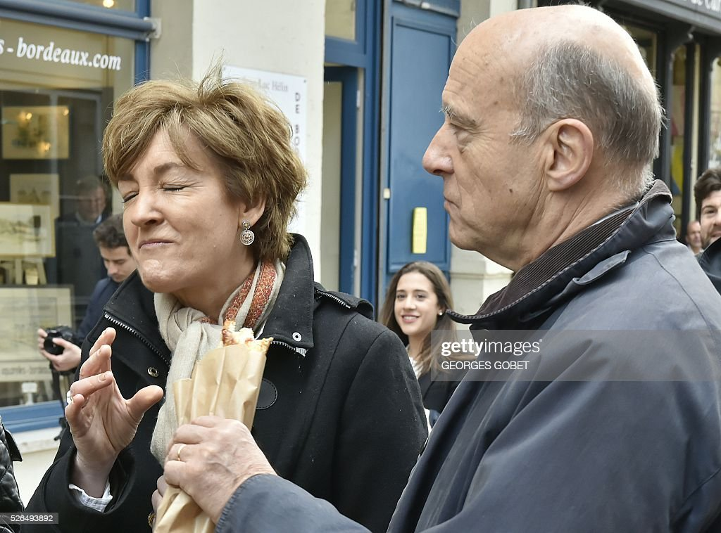 French mayor of Bordeaux and French candidate for the right-wing Les Republicains (The Republicans) presidential primary Alain Juppe eats with his wife Isabelle as they walk in the streets of Bordeaux for the promotional launching of a shopping street in the city centre on April 30, 2016. / AFP / GEORGES