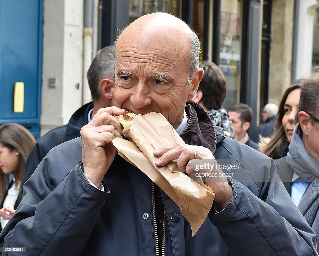 French mayor of Bordeaux and French candidate for the right-wing Les Republicains (The Republicans) presidential primary Alain Juppe eats as he walks in the streets of Bordeaux for the promotional launching of a shopping street in the city centre on April 30, 2016. / AFP / GEORGES