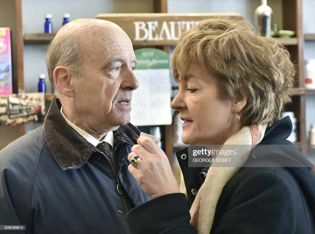 French mayor of Bordeaux and French candidate for the right-wing Les Republicains (The Republicans) presidential primary Alain Juppe speaks with his wife Isabelle as she drinks tea during the promotional launching of a shopping street in the city centre of Bordeaux on April 30, 2016. / AFP / GEORGES