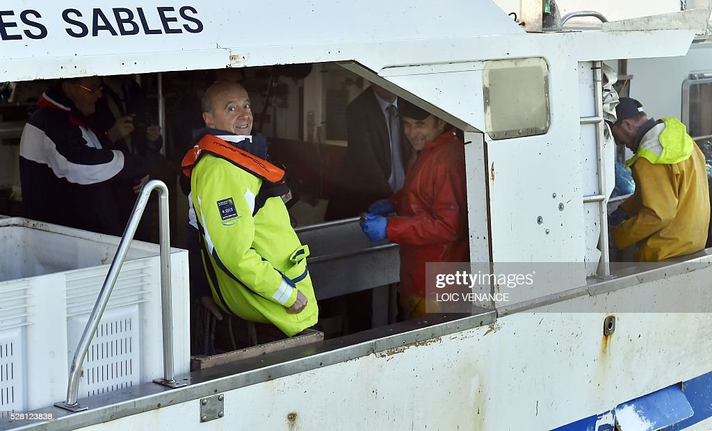 French mayor of Bordeaux and French candidate for the right-wing Les Republicains (The Republicans) presidential primary Alain Juppe (L) sails with fishermen on May 4, 2016 offshore Saint-Gilles-Croix-de-Vie, western France. / AFP / LOIC