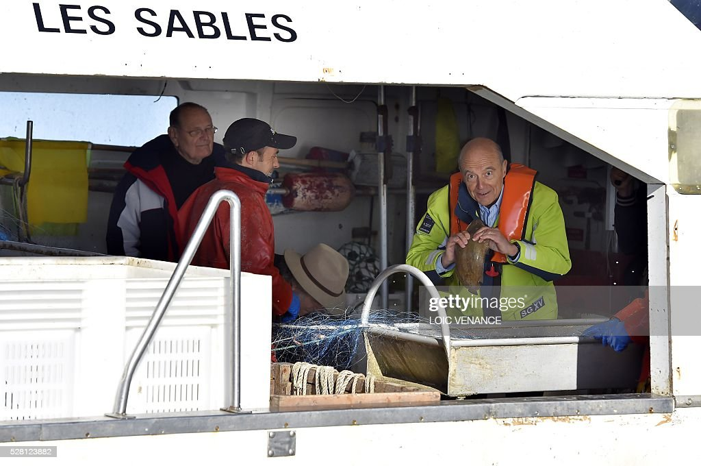 French mayor of Bordeaux and French candidate for the right-wing Les Republicains (The Republicans) presidential primary Alain Juppe (R) sails with fishermen on May 4, 2016 offshore Saint-Gilles-Croix-de-Vie, western France. / AFP / LOIC