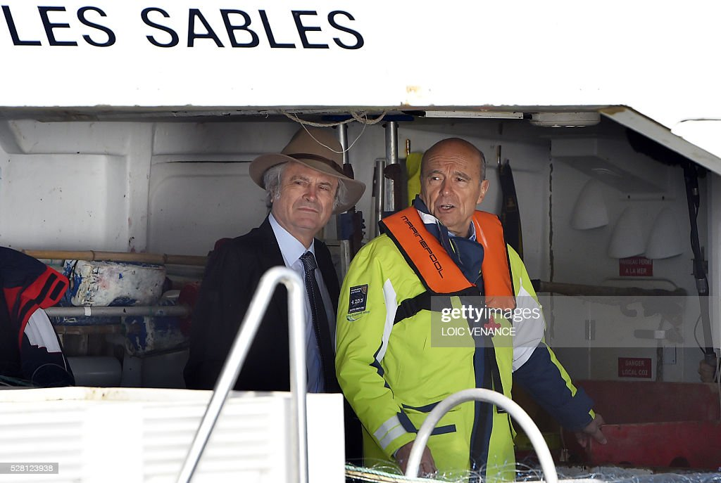 French mayor of Bordeaux and French candidate for the right-wing Les Republicains (The Republicans) presidential primary Alain Juppe (R) and French american journalist Franz-Olivier Giesbert sail with fishermen on May 4, 2016 offshore Saint-Gilles-Croix-de-Vie, western France. / AFP / LOIC