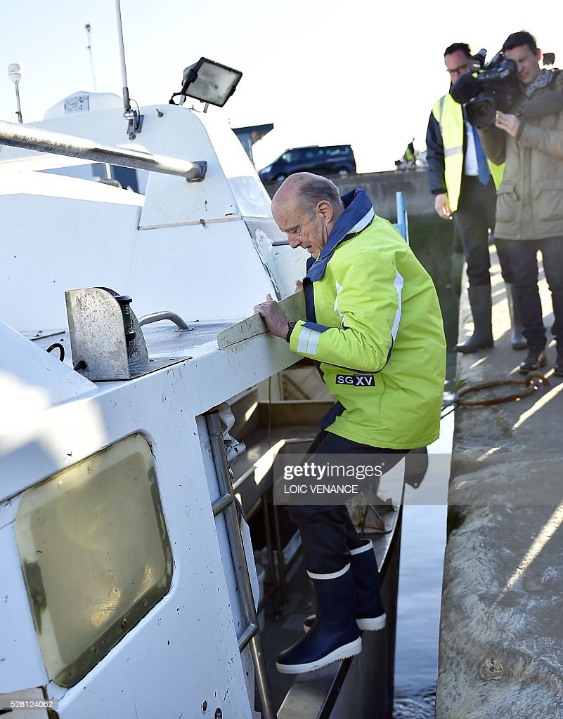 French mayor of Bordeaux and French candidate for the right-wing Les Republicains (The Republicans) presidential primary Alain Juppe boards a fishing boat as part of a campaign visit, on May 4, 2016 in Saint-Gilles-Croix-de-Vie, western France. / AFP / LOIC