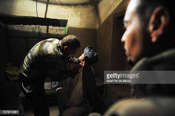 A French medic from the 4th Alpine hunters regiment of Gap treats a man 28 November 2007 in the village of Zemmah in the district of Kalahan some 20...