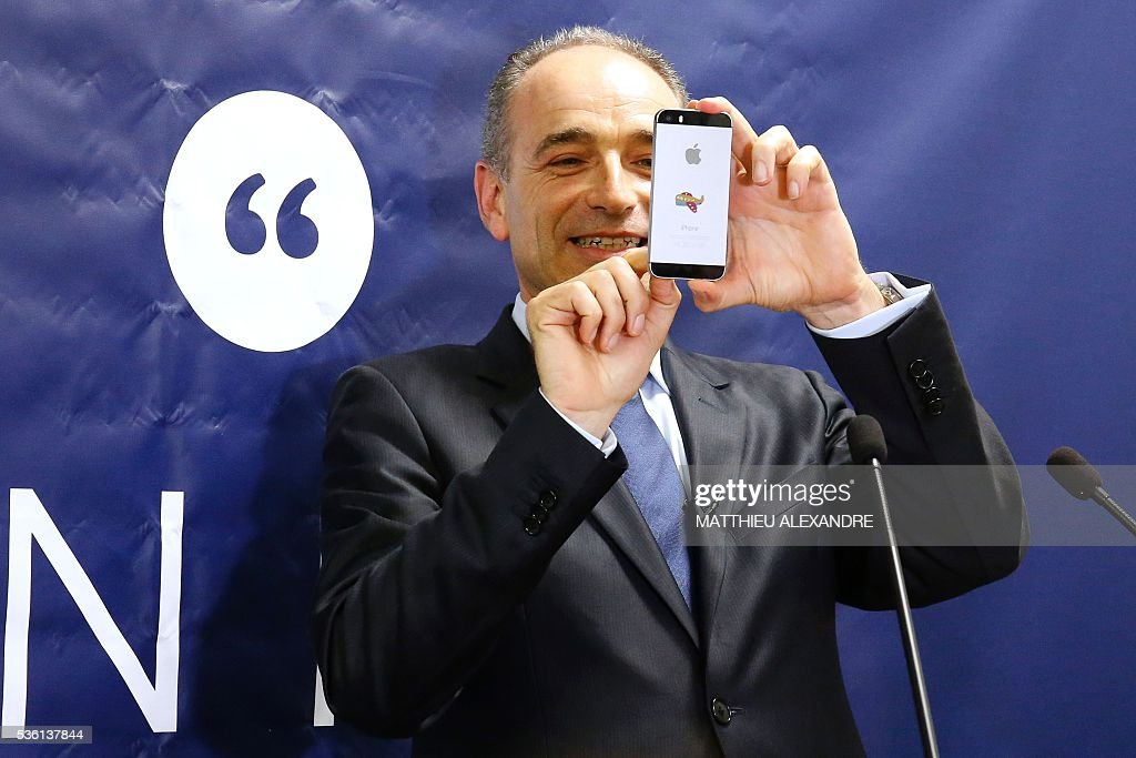 French member of parliament candidate in the right-wing opposition Les Republicains (LR) party primary ahead of France's 2017 presidential elections, Jean-Francois Cope, takes a picture with his phone as he delivers a speech during the inauguration of his election campaign headquarters, on May 31, 2016, in Paris. / AFP / MATTHIEU