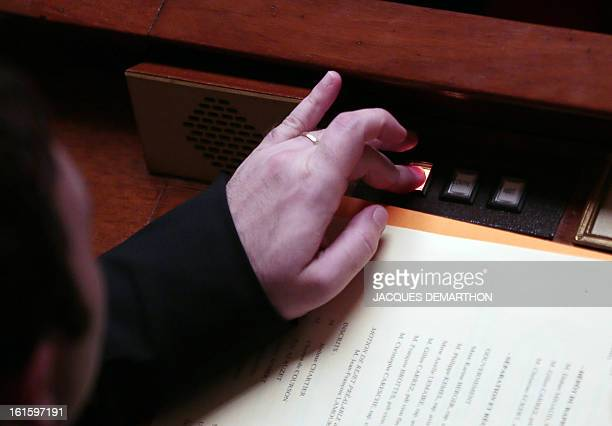 A French member of Parliament pushes a button to vote on February 12 2013 at the French National Assembly in Paris during the vote legalising samesex...