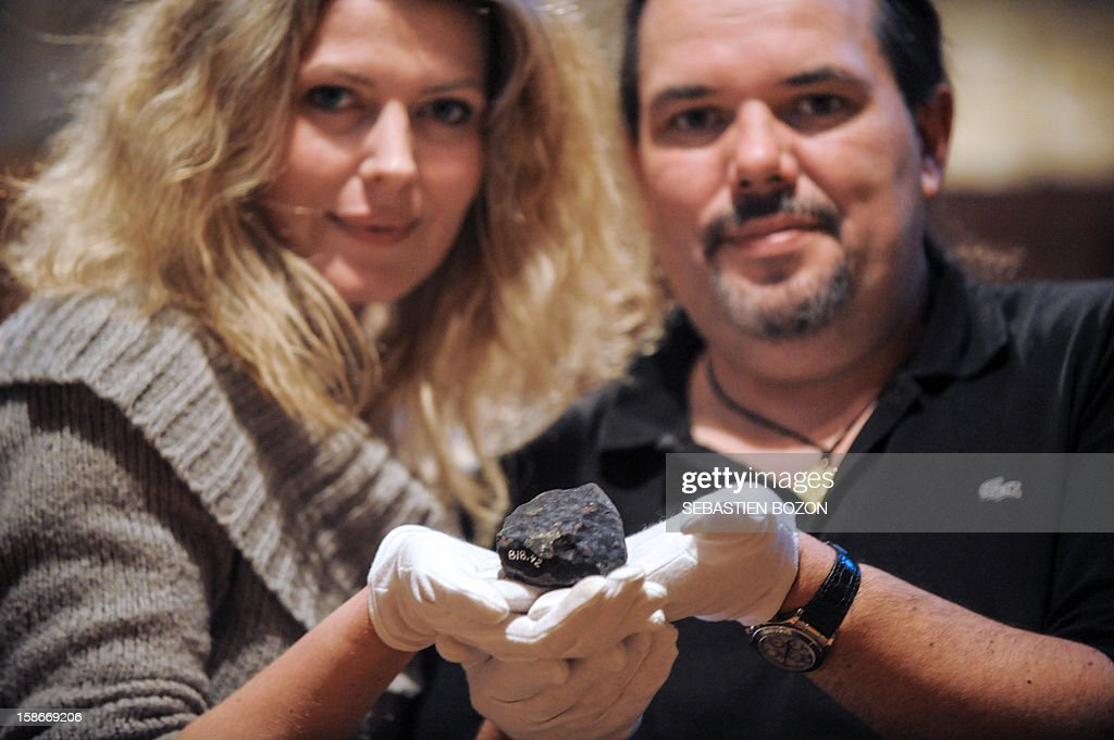 French meteorite seekers Carine Bidaut and Bruno Fectay pose with a meteorite fragment, in Poligny, eastern France, on November 12, 2012. BOZON