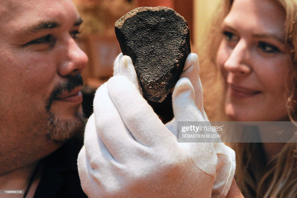 French meteorite seekers Carine Bidaut and Bruno Fectay pose with a meteorite fragment, in Poligny, eastern France, on November 12, 2012.