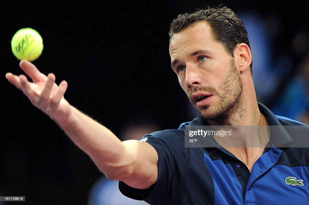 French Michael Llodra eyes the ball as he serves to his opponent French Benoit Paire during the Open Sud de France world tour ATP Series semi final tennis match, on February 9, 2013 in Montpellier, southern France. Paire won 4-6, 6-3, 6-1. AFP PHOTO / SYLVAIN THOMAS