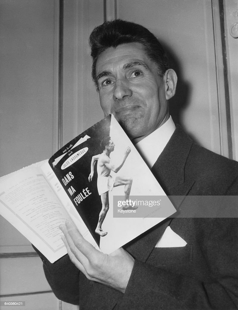 French middledistance runner Jules Ladoumègue with his autobiography 'Dans ma foulée' after it won the prize for sport literature from the French...