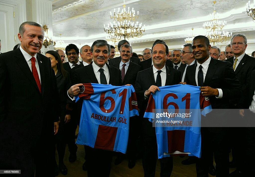 French midfielder Florent Malouda (2nd R) of Trabzonspor football team, presents the team jerseys to French President Francois Hollande (3rd R) and Turkish President Abdullah Gul (2nd L) during a dinner in honor of Hollande at Cankaya Presidential Palace in Ankara, Turkey, on January 27, 2014. Turkish Prime Minister Recep Tayyip Erdogan (L) attends the dinner.