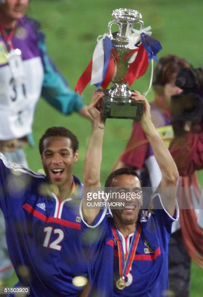 French midfielder Youri Djorkaeff hods up the Euro2000 soccer championships trophy as he is followed by his teammate Thierry Henry after France won...